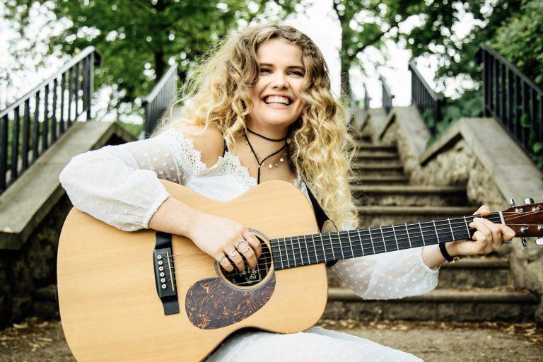 Daisy Clark press photo with a guitar