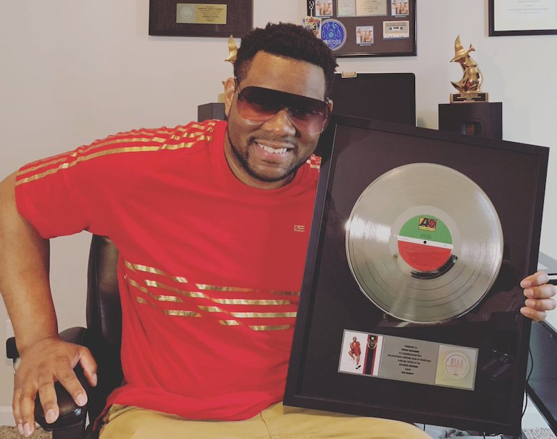 Mr. Talkbox press photo holding 3x's Platinum Plague for 24K Magic