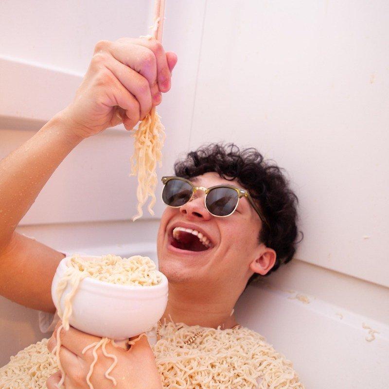 Lil Noodle press photo with noodles