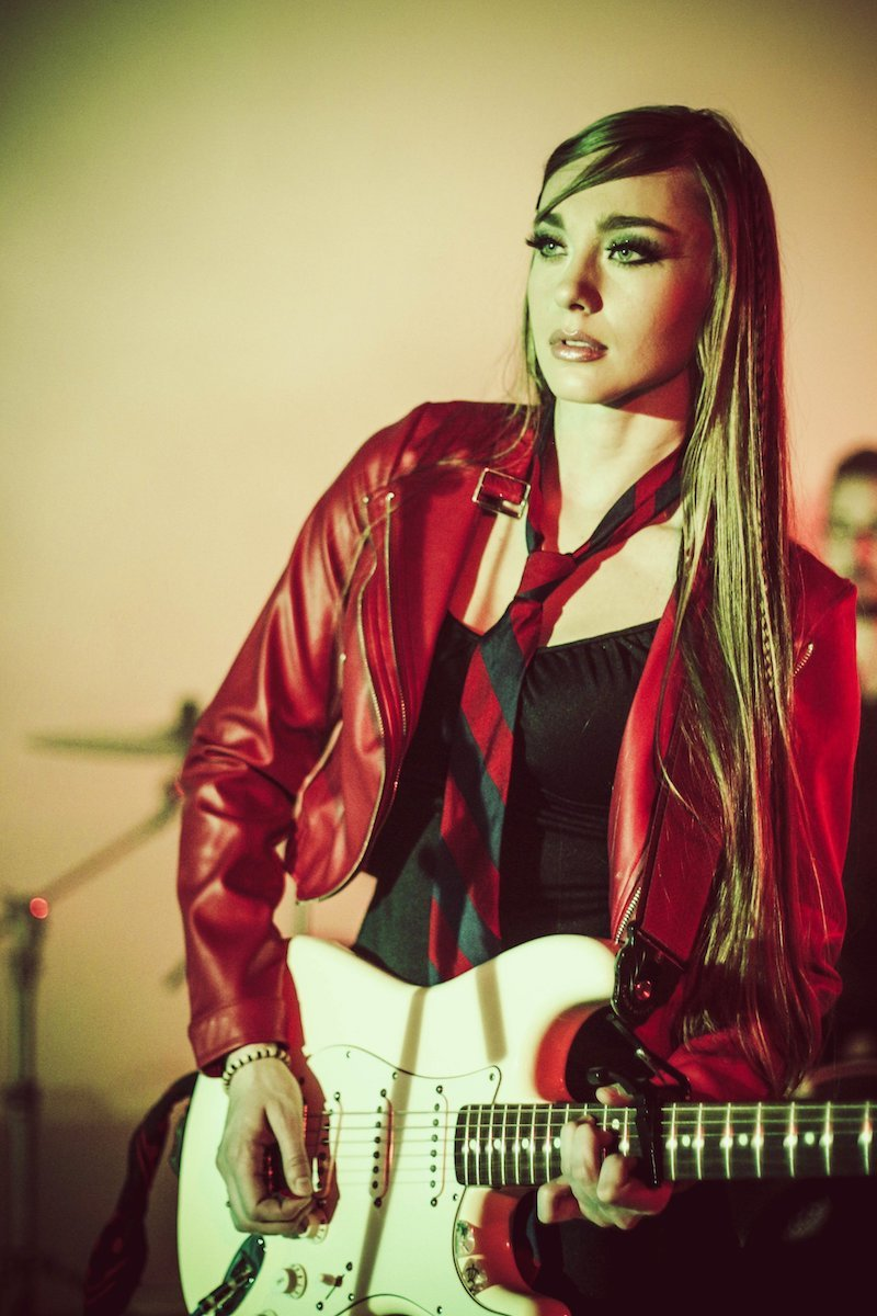 Madison Roe press shot with a guitar
