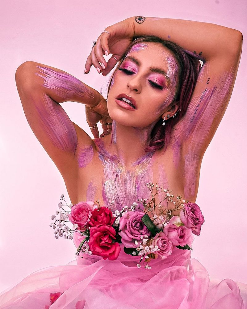 "Beth McCarthy ""She Gets the Flowers"" press photo with face and body painted and roses decorated around her chest area"