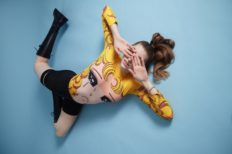 Betta Lemme - Cry press photo with blue background and knee-high boots.