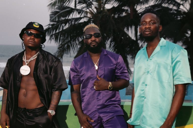 """Blaq Jerzee, Mr Eazi, and Harmonize - """"Falling For U"""" press photo with the ocean in the background."""