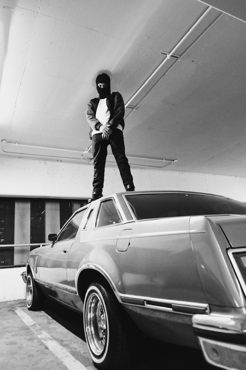 Clyde Guevara press photo standing on top of an old-school vehicle parked in a commercial garage area.