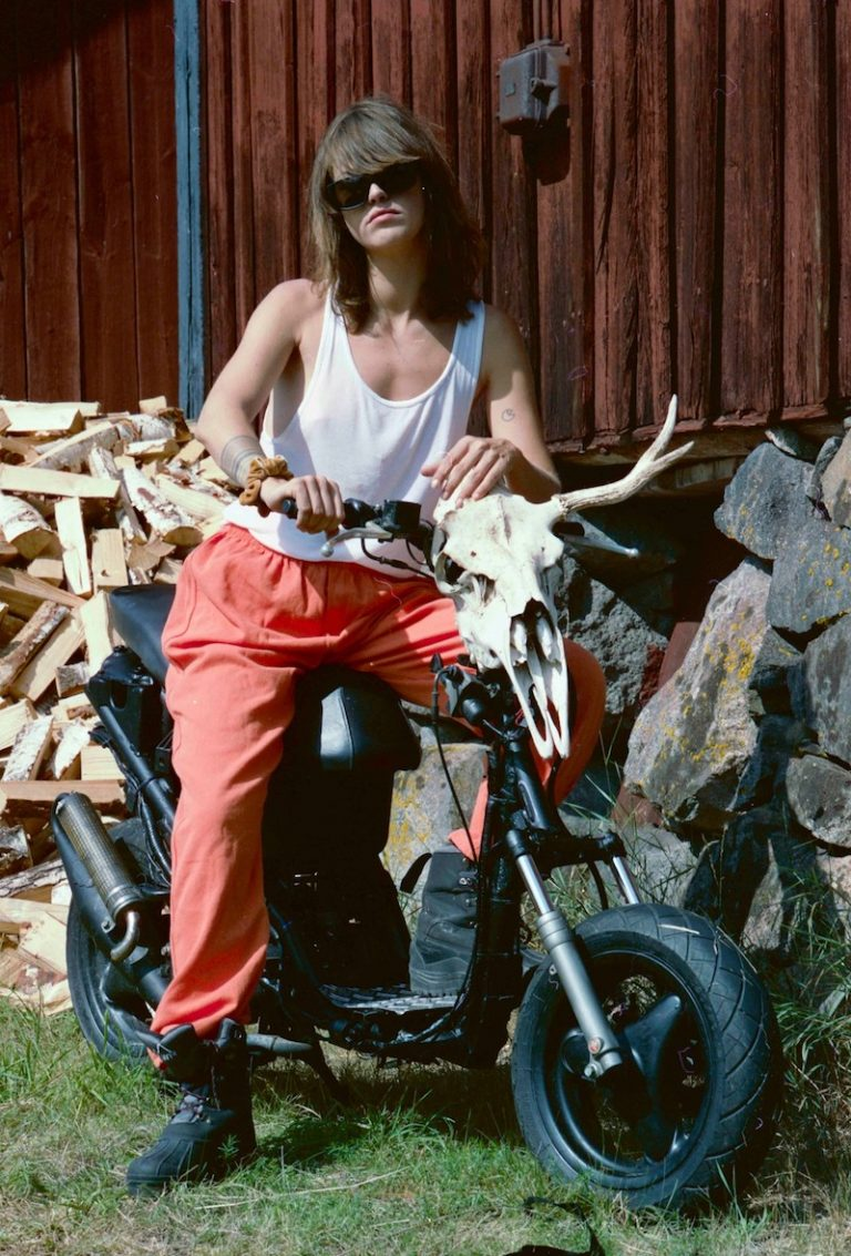 "Elliphant - ""Notorious"" press photo sitting on a black motorbike with an animal skull attached to the handle bar."