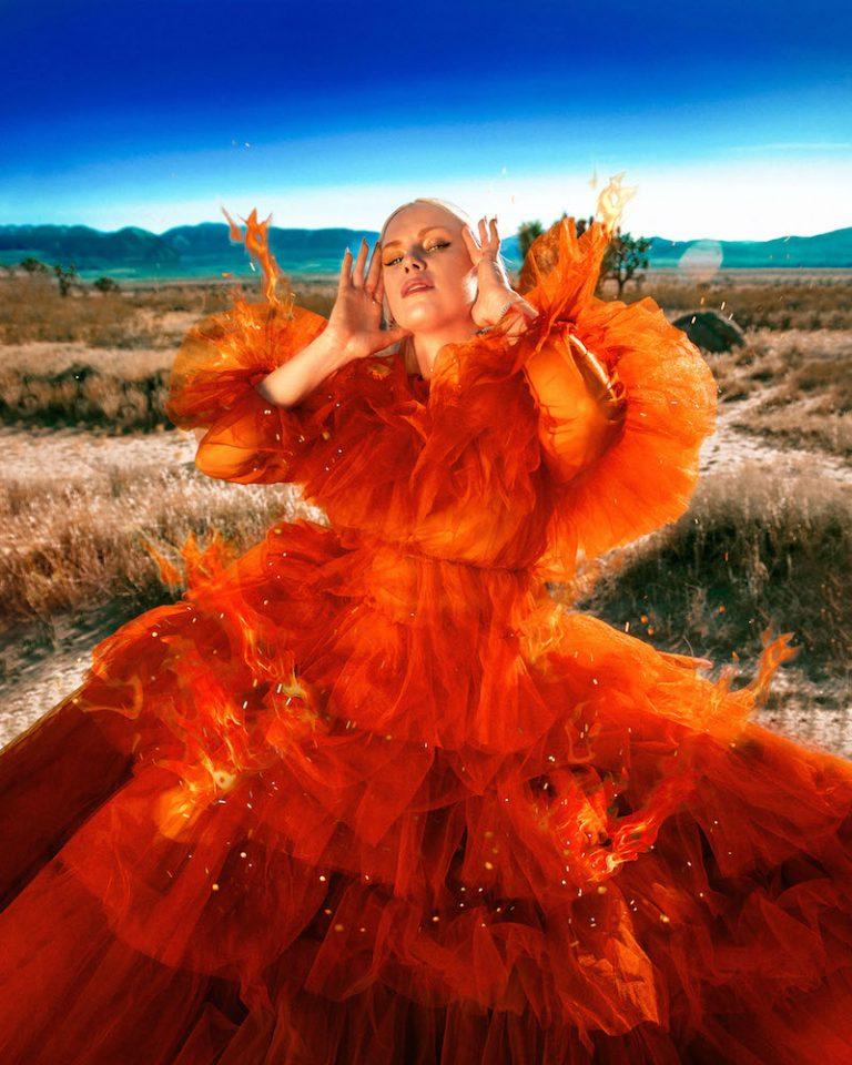 """Grace Weber - """"Thru the Fire"""" press photo outside wearing a fiery orange outfit"""