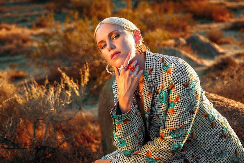 """Grace Weber - """"Thru the Fire"""" press photo outside wearing a colorful outfit."""