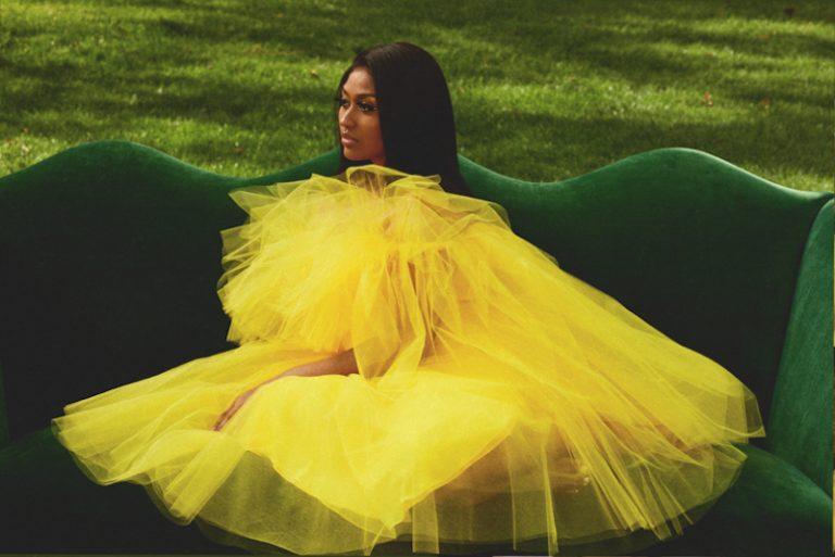 "Jazmine Sullivan - ""Girl Like Me"" cover press photo wearing a yellow dress."