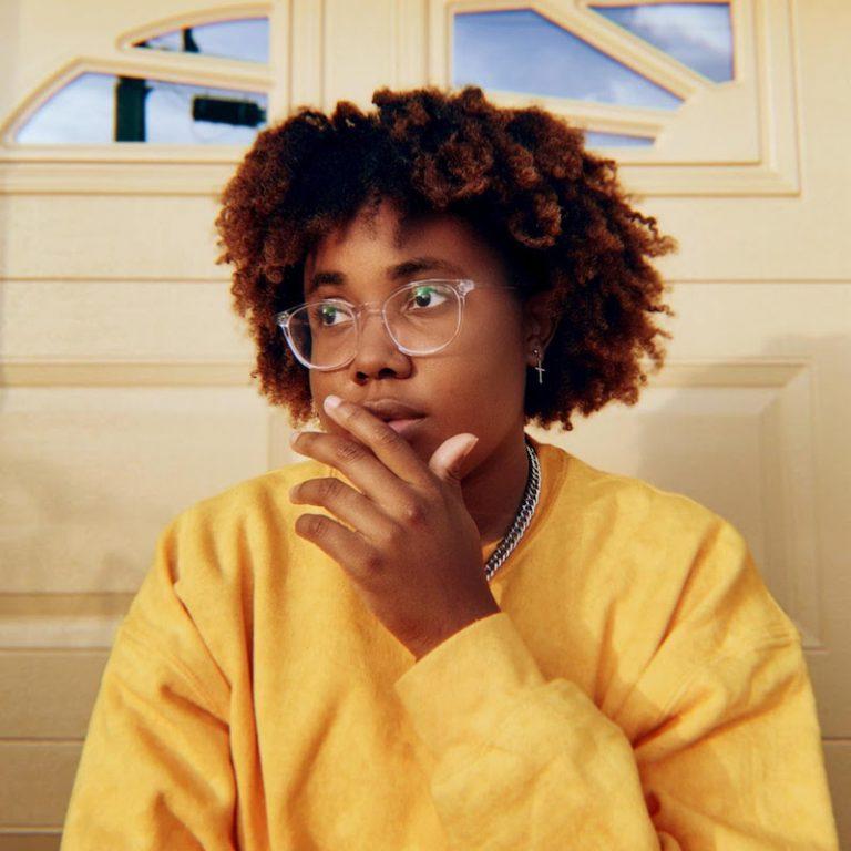 Justy press photo wearing a yellow sweater.