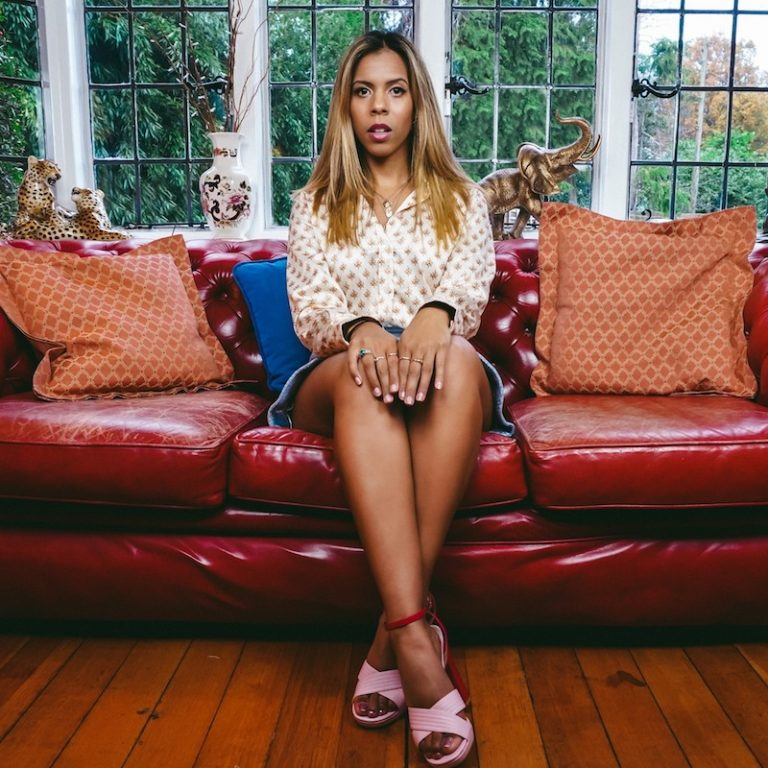"""Kelli-Leigh's """"You Don't Know Me"""" press photo sitting on a sofa."""