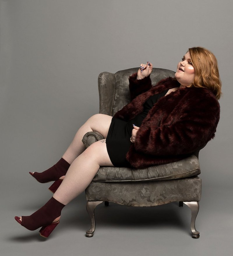 MaKenzie Thomas press photo sitting in a stylish chair.