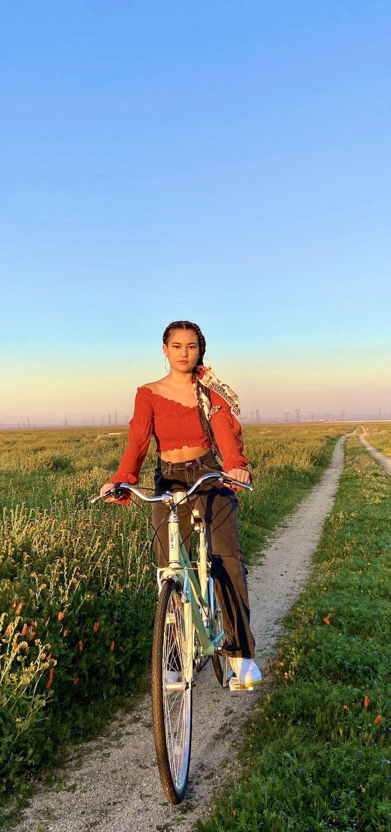 Naomicheyanne riding a pedal bike in an open field.