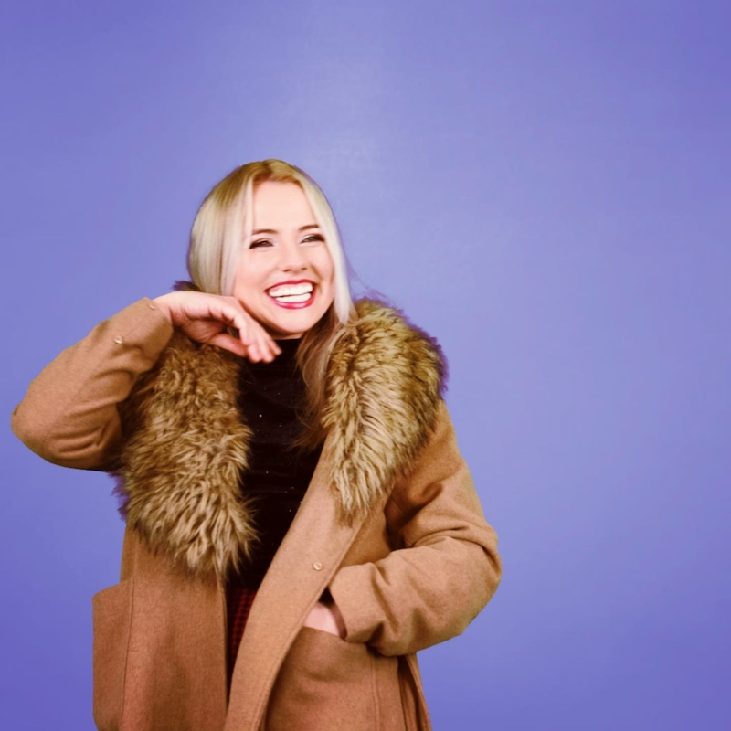 Sarah O'Moore press photo laughing with a purple background