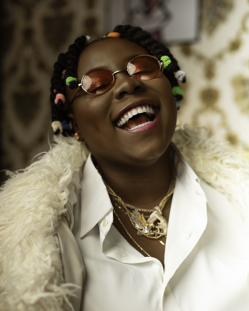 Teni The Entertainer press photo laughing wholeheartedly like she just won a million dollars.