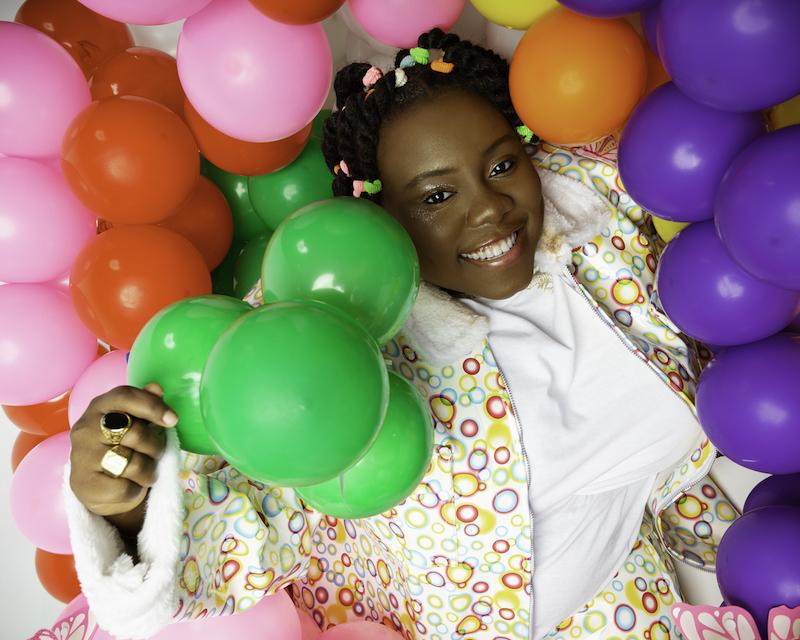 Teni The Entertainer joyful press photo with colorful balls.