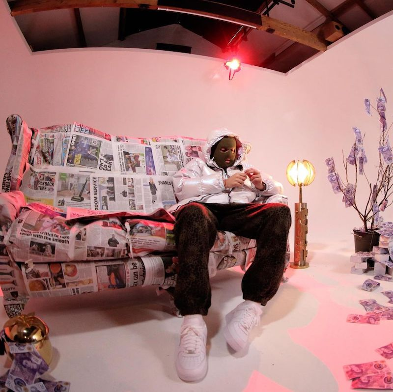 UKNWN press photo sitting on a sofa wrapped in newspaper.