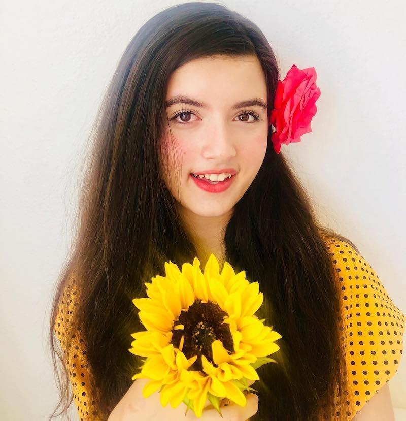 Angelina Jordan press photo holding a sunflower