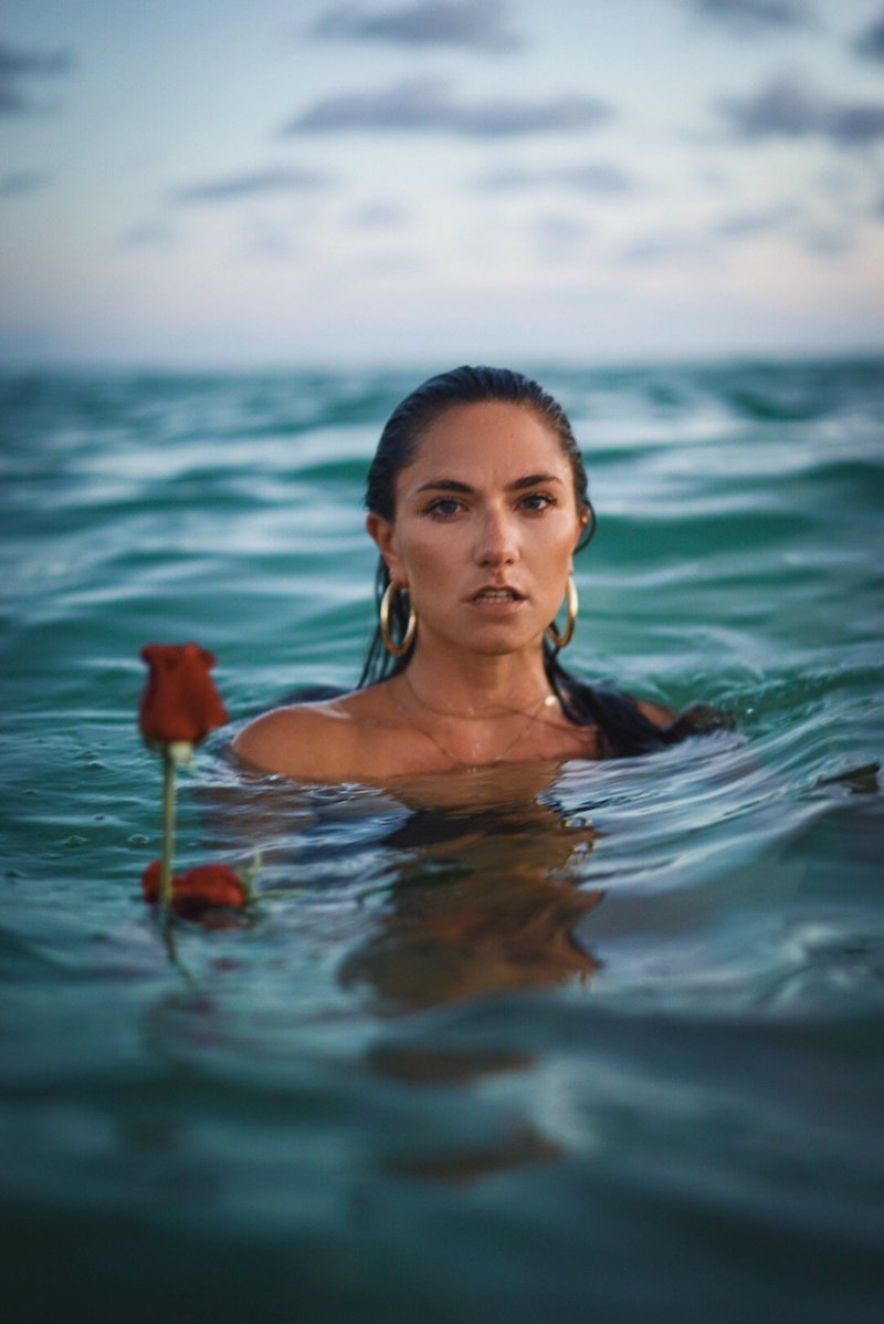 Camille Trust press photo swimming in the ocean beside a floating red rose