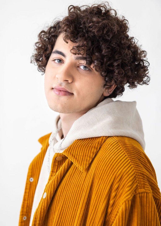 Issam Alnajjar press photo wearing a white hoodie and brownish jacket