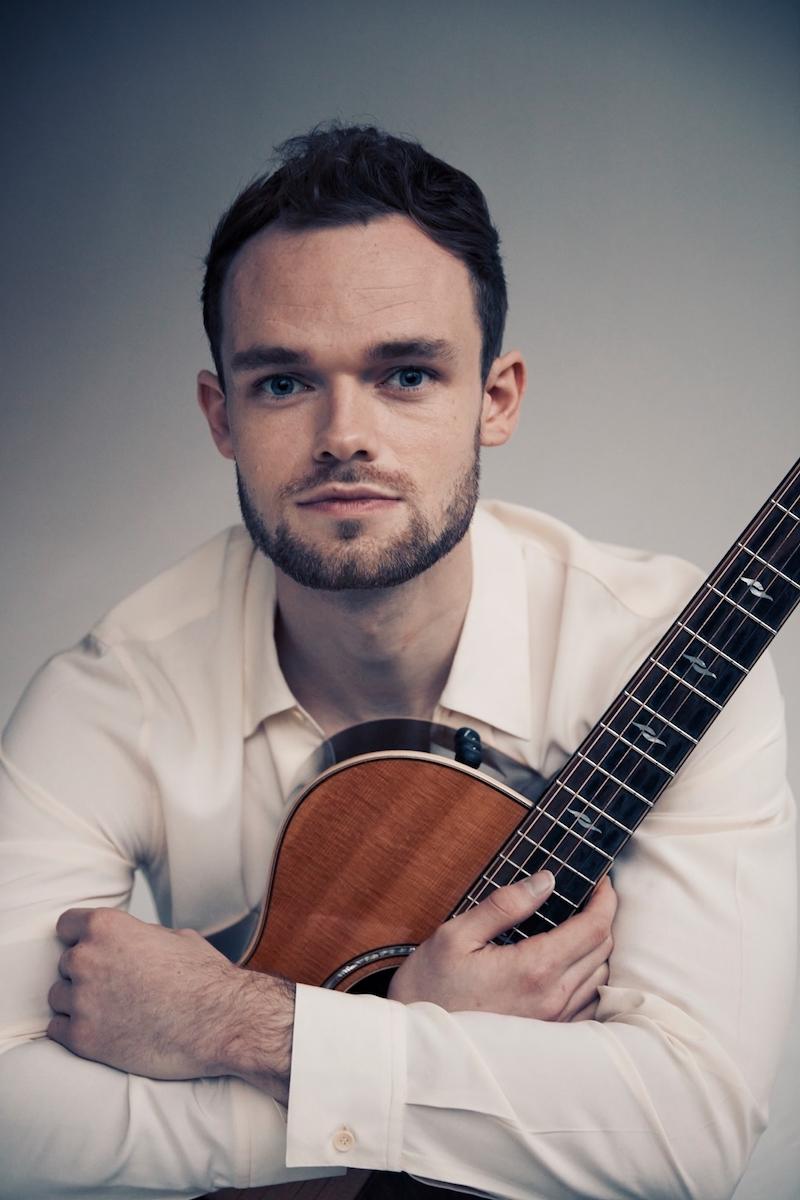 James TW press photo holding a guitar