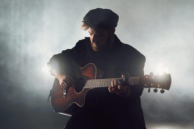 John Adams press photo playing a guitar