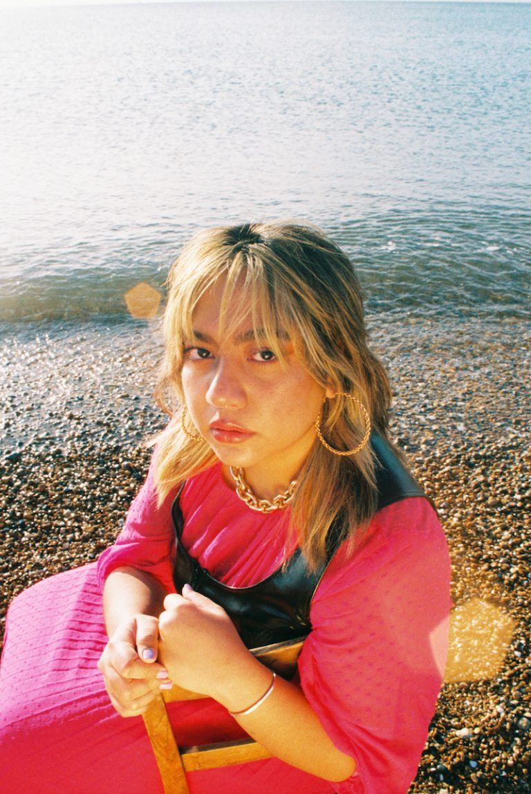 "Kaisha - ""Predicament"" press photo outside with a large body of water in the background"