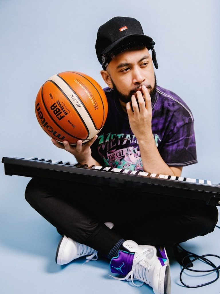 KyleYouMadeThat press photo holding a basketball and a keyboard resting on his lap