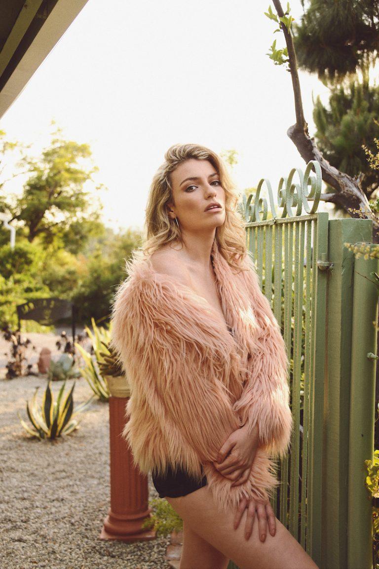 Lola Lennox WYG press photo outside wearing a stylish pink coat