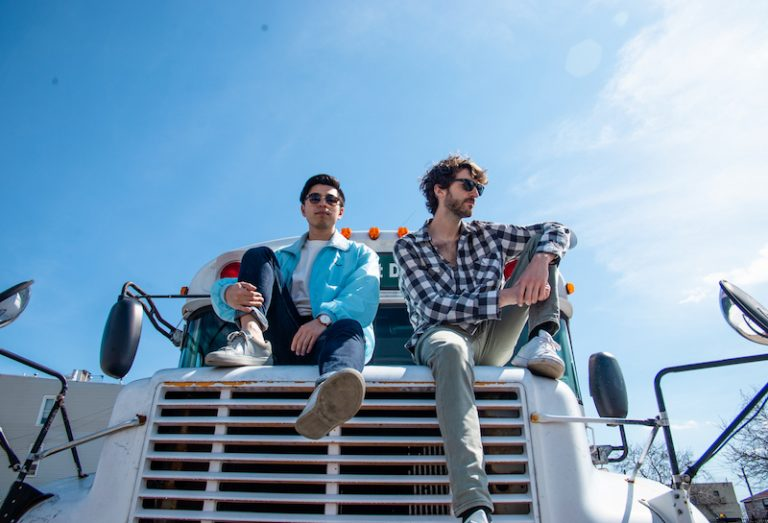 Max & Lamour press photo in Red Hook sitting on the hood of an old-fashioned bus