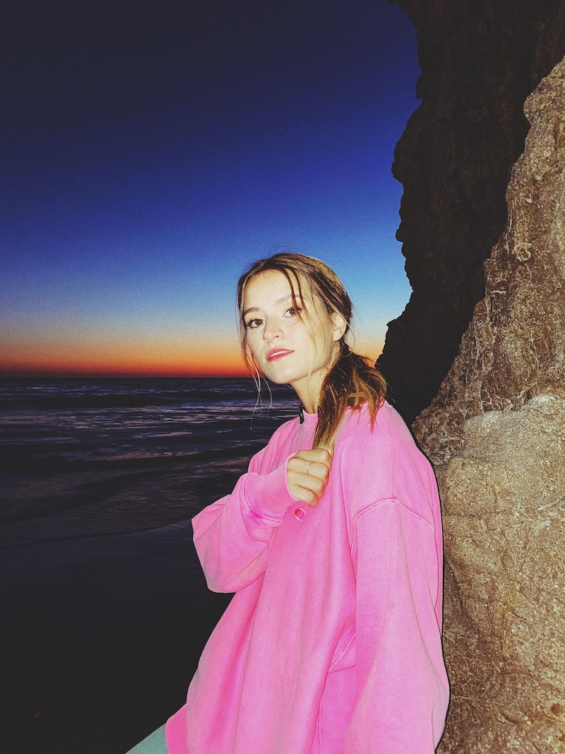 Rosie Darling press photo wearing a pink sweatshirt with a body of water in the background