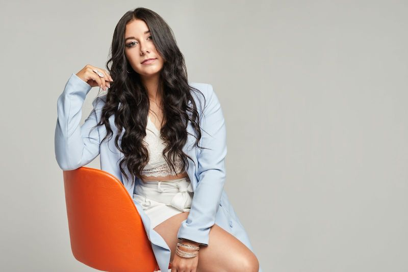 Shantaia press photo sitting on an orange chair