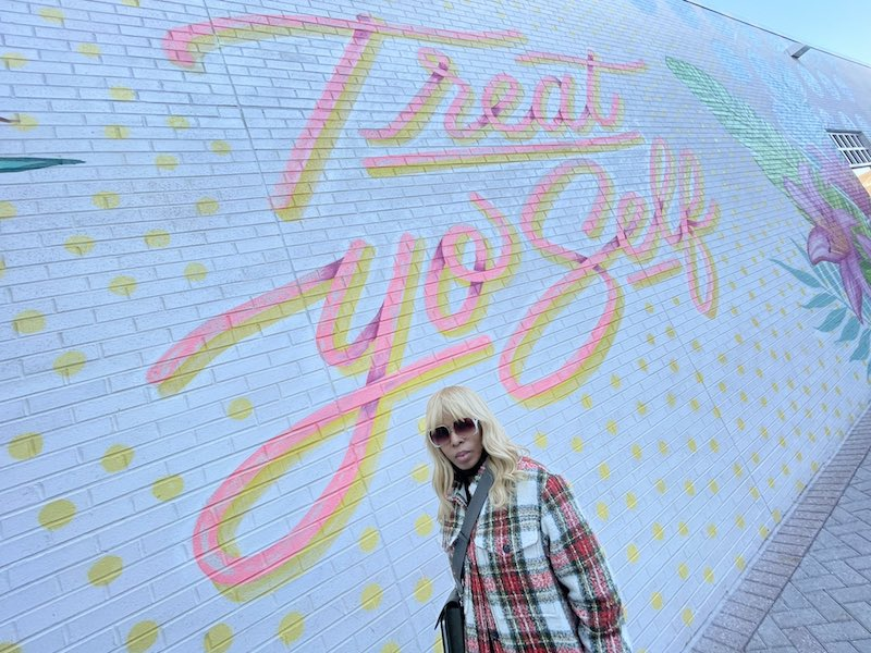 """Sparkle press photo outside by a """"Treat Yo Self"""" graffiti wall"""