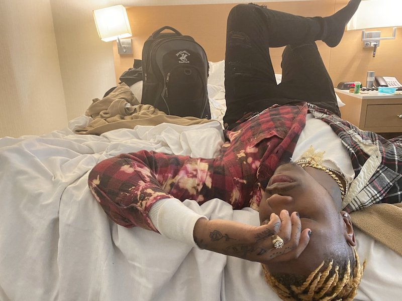 Taythedxn press photo laying on a bed