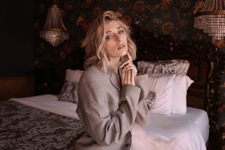 """VÉRITÉ - """"By Now"""" press photo on top of a well-dressed bed"""