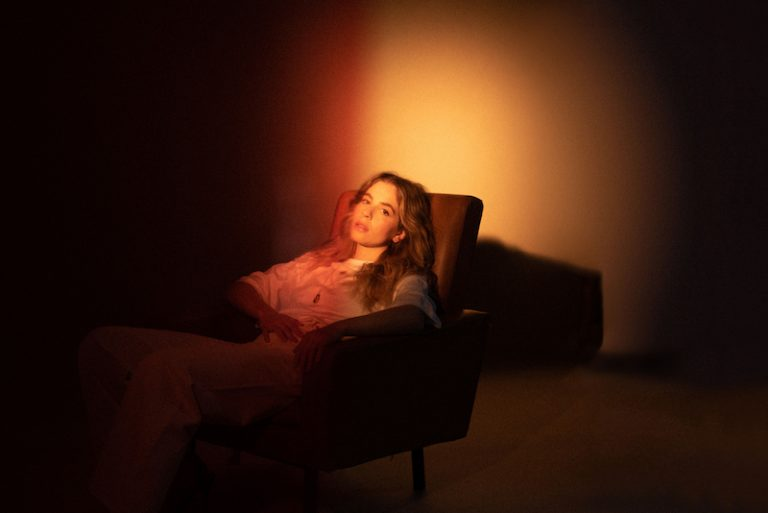 emie nathan press photo sitting in a chair in the dark