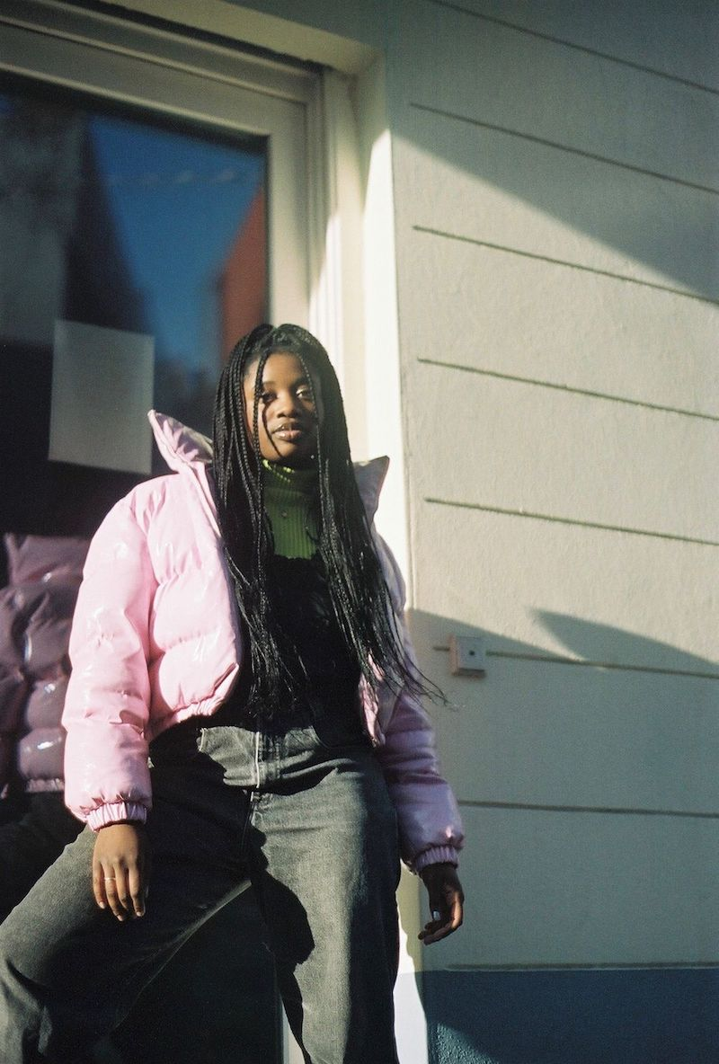 Abby T press photo wearing a pink coat/jacket
