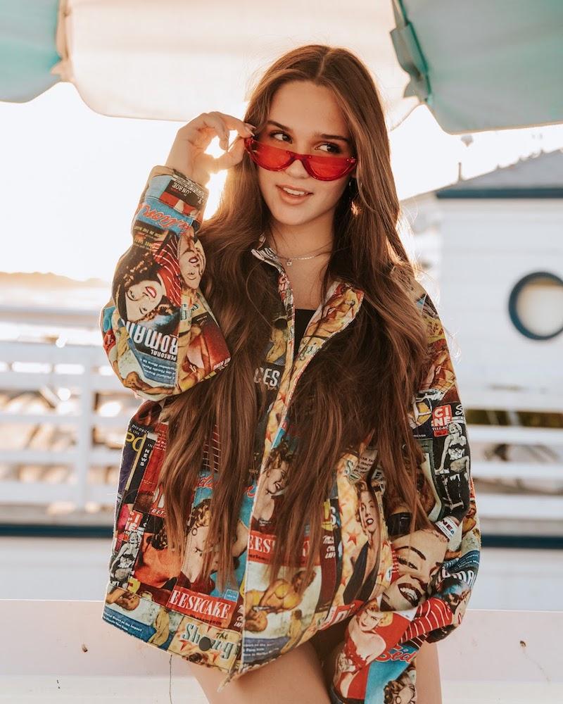 Amelie Anstett press photo wearing an oversized pop culture/magazine printed jacket