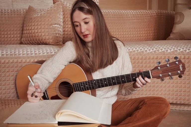 Annabel Gutherz press photo writing and holding a guitar