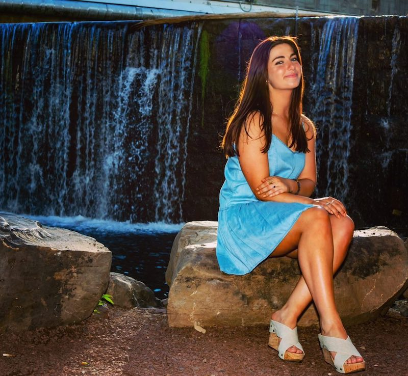 Capri press photo sitting on a rock with a waterfall in the background
