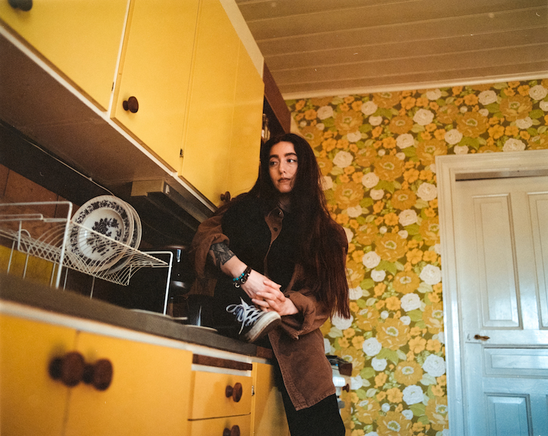 """Elina - """"Love Come Around"""" press photo inside a yellow-themed kitchen"""