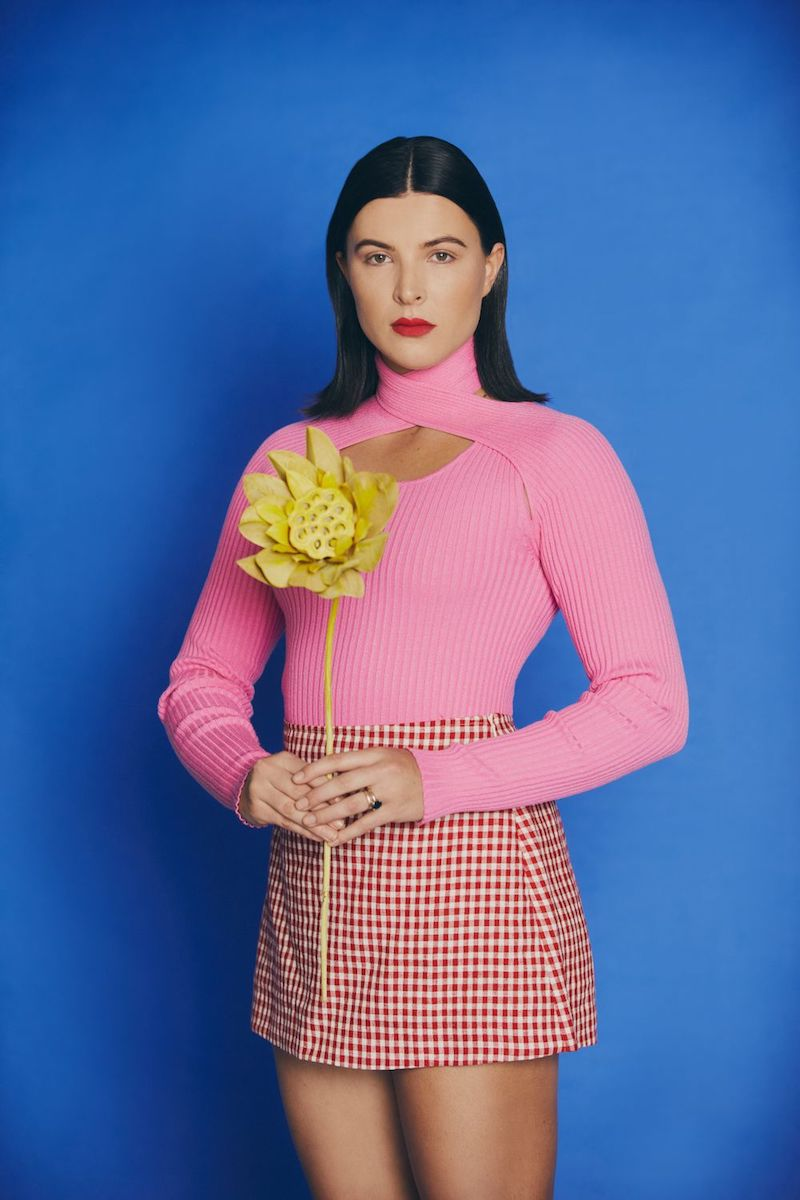 Georgia Lines press photo with a blue background holding yellow flowers