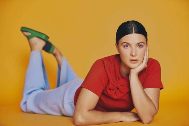 Georgia Lines press photo laying on her stomach wearing a red and blue outfit