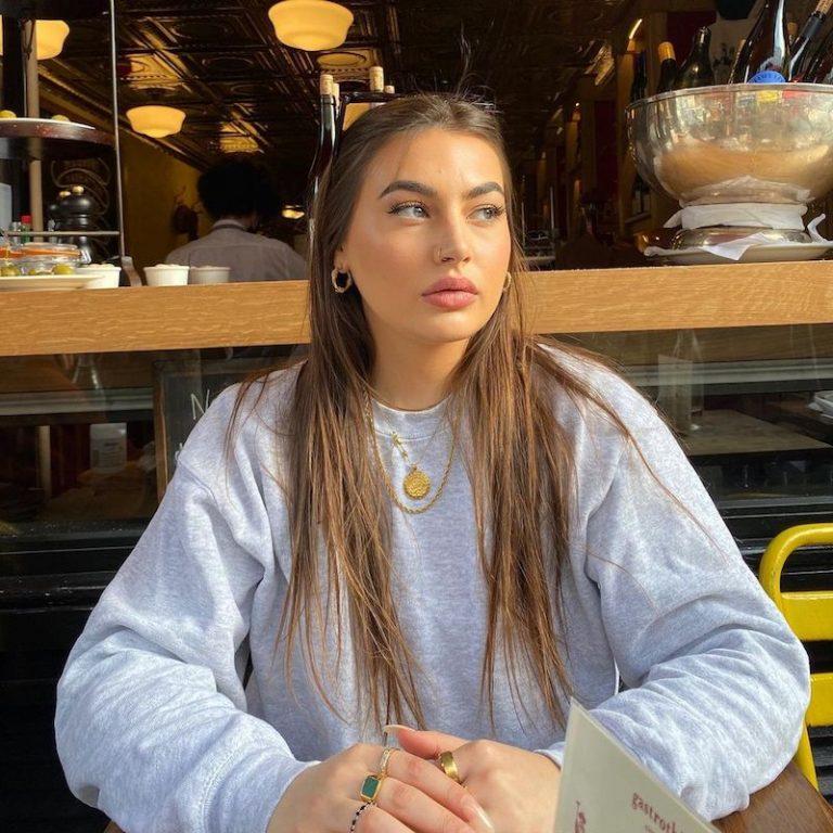 Gigi Moss press photo wearing a grey sweatshirt while seated inside an eatery