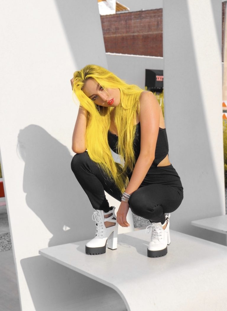 KINGS press photo with yellow hair and black outfit