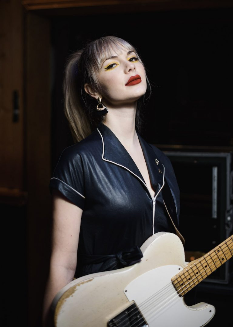 Kandle press photo wearing a black outfit and holding a guitar