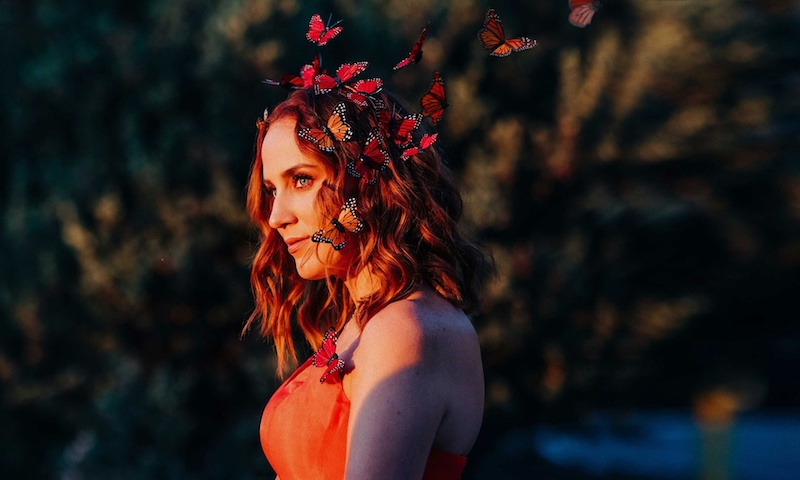 Kara Connolly Something More press photo outside with butterflies