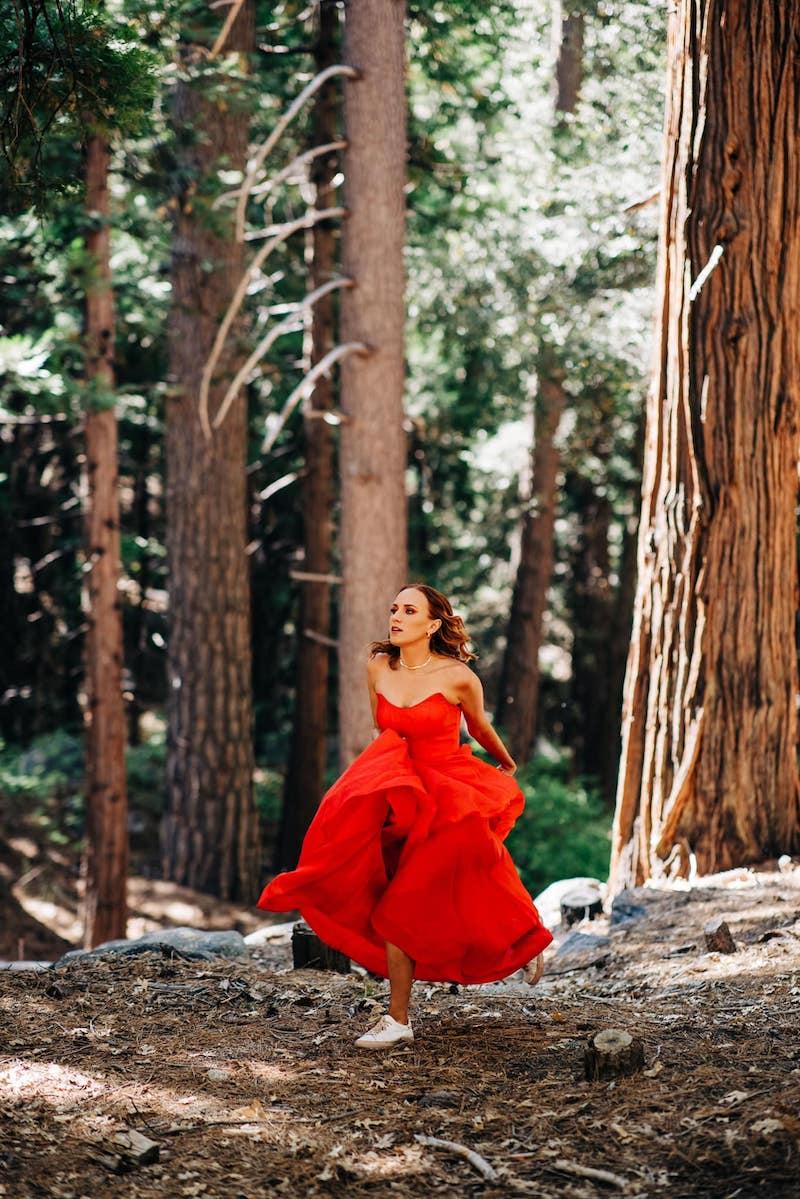 Kara Connolly press outside wearing a reddish-orange dress