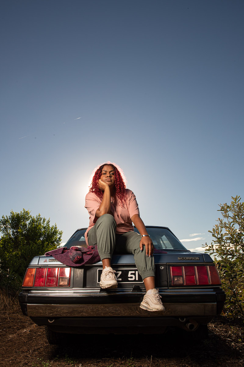 """Miiesha - """"Damaged"""" press photo sitting outside on the truck of a car"""