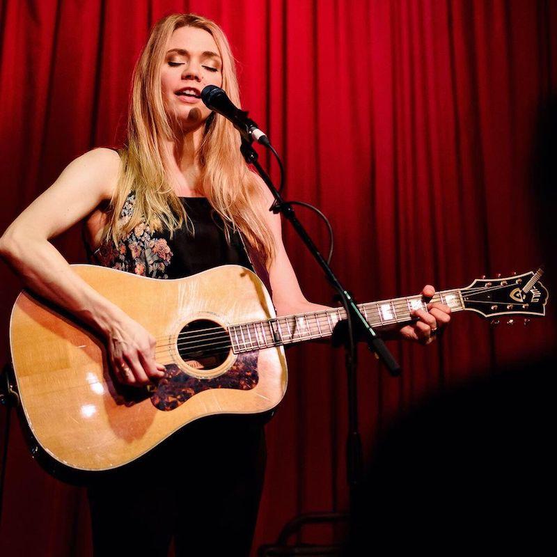 Natalie Gelman press photo singing while playing a guitar