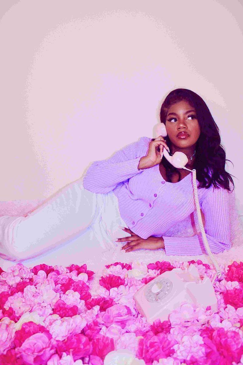 RAYRAY press photo wearing a purple sweater and white pants